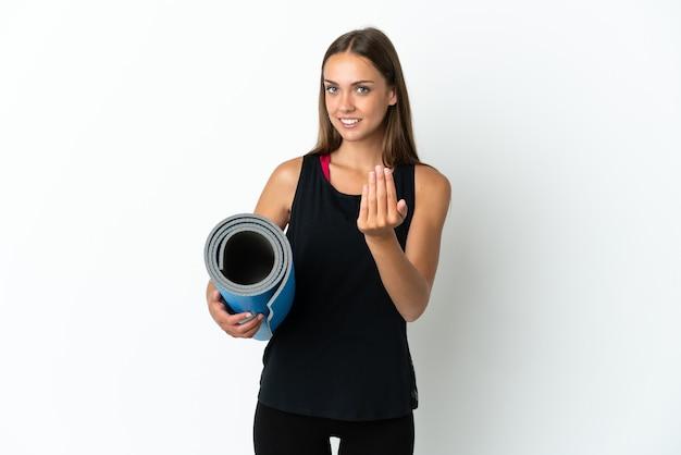 Sport kobieta idzie na zajęcia jogi, trzymając matę na białym tle, zapraszając do przyjścia z ręką. cieszę się, że przyszedłeś
