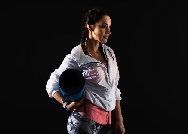 Sport kobieta na ciemnym tle z matą