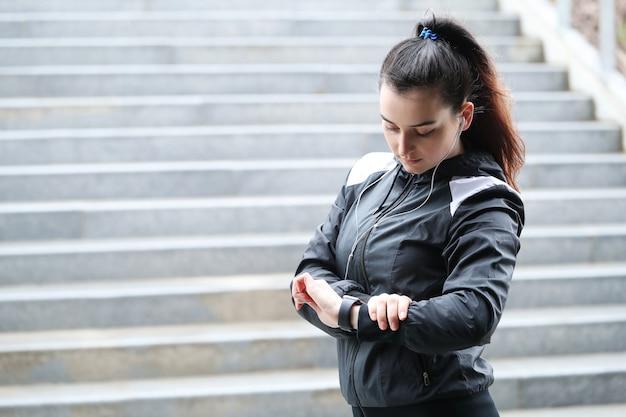 Sport kobieta plenerowy patrzeć jej zegarek na rękę