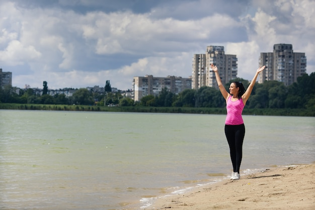 Sport kobieta podnosi ręce w pobliżu jeziora
