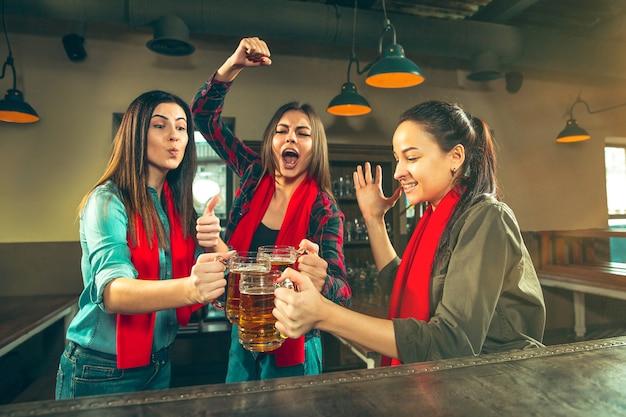 Sport, ludzie, wypoczynek, przyjaźń, rozrywka - szczęśliwe kibice lub dobre młode przyjaciółki pijące piwo, świętujące zwycięstwo w barze lub pubie. koncepcja ludzkich pozytywnych emocji