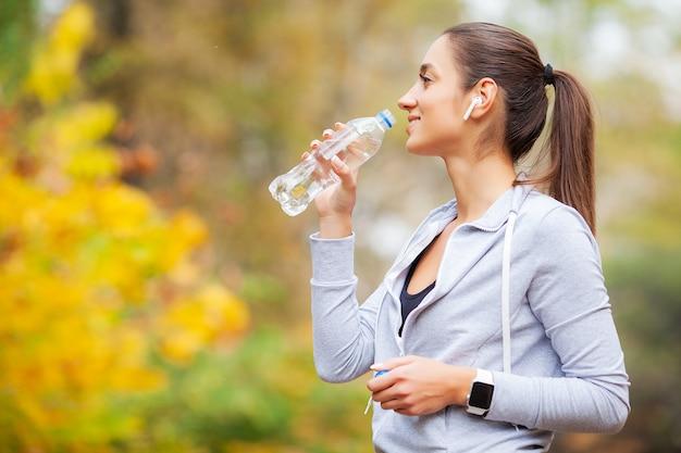 Sport na świeżym powietrzu. kobiety woda pitna po biegać