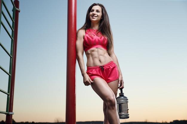 Sport na świeżym powietrzu piękny silny seksowny atletyczny muskularny młody kaukaski kobieta fitness z butelką wody do picia na treningu treningu