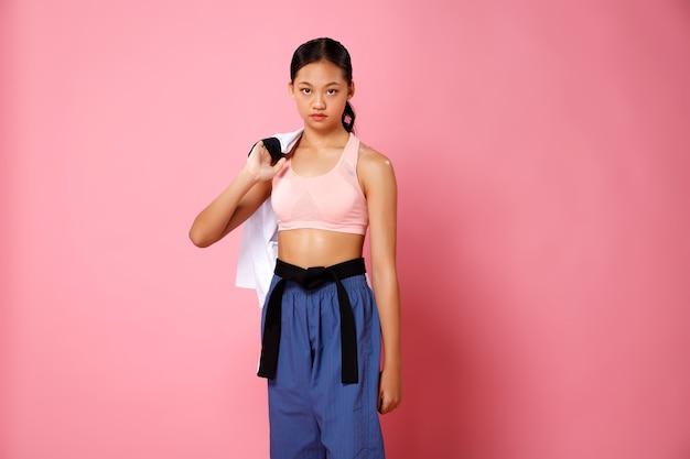 Sport nastolatek dziewczyna trzymać mundur yukata i patrzeć na kamery. 12-15 lat azjatyckich sportowców młodzieżowych dzieciak nosi pastelowe różowe spodnie z tkaniny fitness na różowym tle pełnej długości!