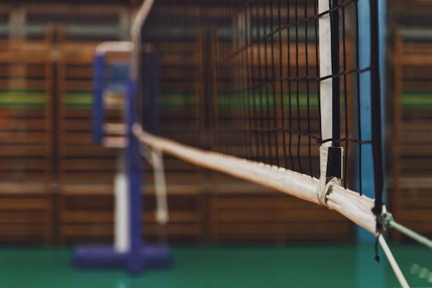 Sport obraz siatki do siatkówki w starej pustej hali sportowej z wieżą sędziowską. tło dla gry zespołowej w siatkówkę. koncepcja uzyskania sportu, zdrowego stylu życia i sukcesu zespołowego. skopiuj miejsce