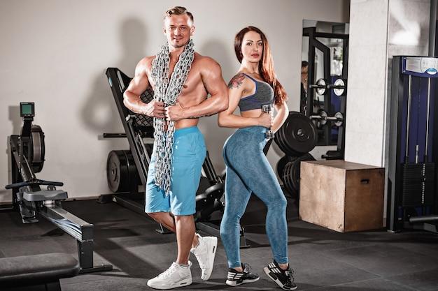 Sport pasuje para na siłowni. praca w parach z hantlami