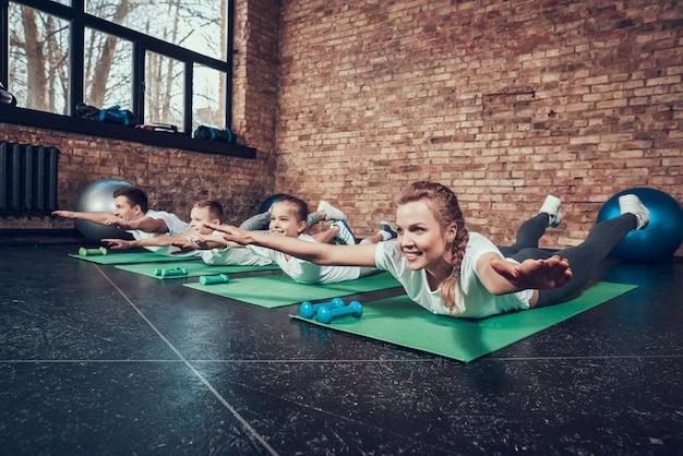 Sport rodzina kładzie się na żołądkach na dywanach siłowni