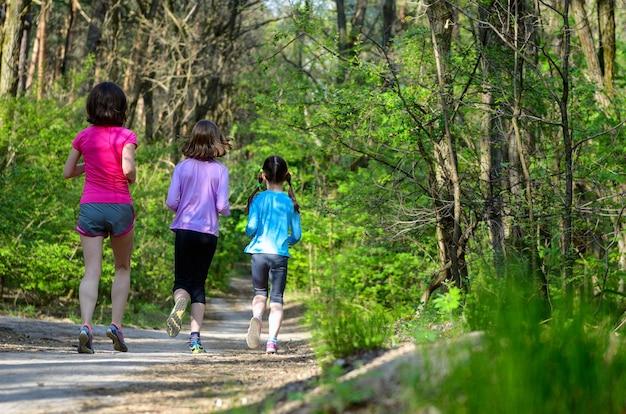 Sport rodzinny, szczęśliwa aktywna matka i dzieci biegające na świeżym powietrzu, biegające w lesie