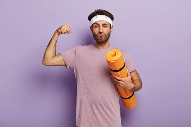 Sport to moje życie. nieogolony mężczyzna ma trening na siłowni