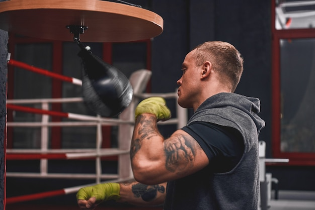 Sport to sposób na życie profesjonalnego młodego boksera do treningu ramion uderzającego