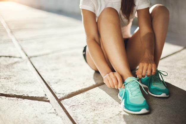 Sport to sposób na życie. zbliżenie: trampki biegacza, wiązanie sznurówek, przygotowywanie się do biegania. koncepcja sportu miejskiego.