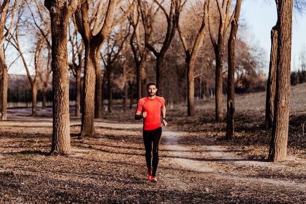 Sport uciekinier w bieg przełajowy. dopasuj męski biegacz do ćwiczeń i skakania na świeżym powietrzu w pięknej górskiej scenerii. sporty i rekreacja