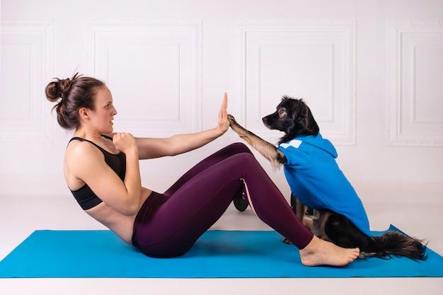 Sport z psem atrakcyjna dziewczyna ćwicząca z psem na niebieskiej macie fitness