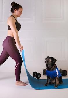Sport z psem. atrakcyjna dziewczyna pracuje na matę fitness niebieski z psem. wysportowana kobieta robi ćwiczenia. siła i motywacja, sport i zdrowy tryb życia. kobieca sprawność.