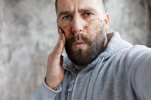 Sport, zdrowie, ludzie, emocje, koncepcja stylu życia - przystojny mężczyzna z trzema różnymi maseczkami na twarz maski czekoladowe, kremowe i gliniane. zdjęcie mężczyzny o doskonałej skórze. sam się pielęgnuje