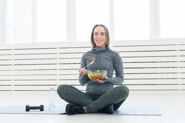 Sport zdrowy styl życia i koncepcja ludzi młoda kobieta z sałatką i hantle siedzącą na