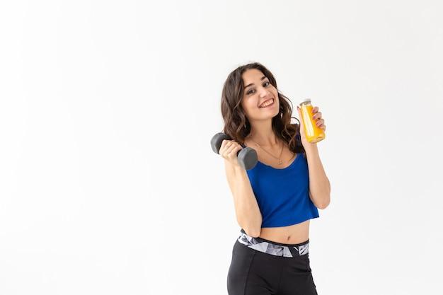 Sport, zdrowy styl życia, koncepcja ludzie - młoda kobieta trzyma butelkę soku i hantle na białym tle z miejsca kopiowania.