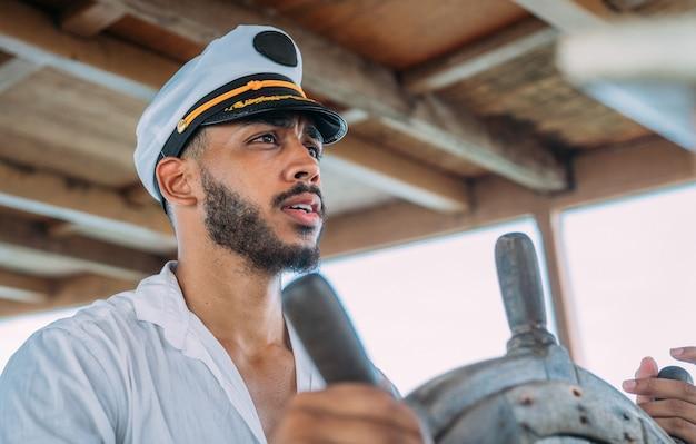 Sport żeglarski. kapitan dowodzący. człowiek ameryki łacińskiej w kapeluszu kapitana statku