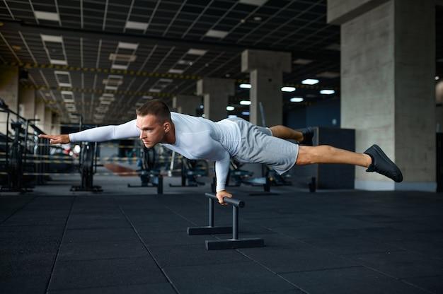 Sportive człowiek robi ćwiczenia abs, trening fitness w siłowni. wysportowany mężczyzna na treningu, sportowiec w klubie sportowym, aktywny zdrowy tryb życia, dobre samopoczucie fizyczne