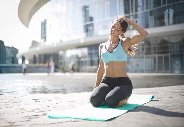 Sportive dziewczyna robi joga na ulicy