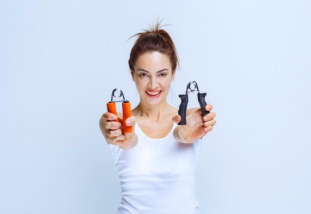 Sportive dziewczyna trzyma uchwyty w kolorze czarnym i pomarańczowym.