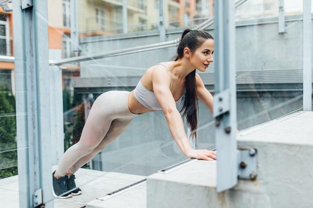 Sportive, fitness kobieta trening robi nogi podwyższone pompki na schodach parku miejskiego. zmotywowana lekkoatletka ciężko trenująca.