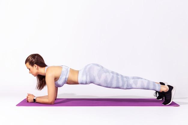 Sportive kobieta ćwiczy jogę, robi ćwiczenia ardha phalakasana, robi deskę, trenuje mięśnie.