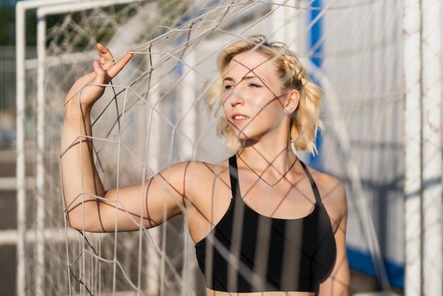 Sportive kobieta przy stadium mienia bramy siecią