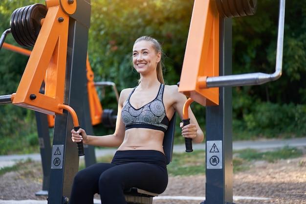 Sportive kobieta przyrząd do ćwiczeń treningowych na świeżym powietrzu w parku letnim