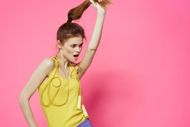 Sportive kobieta skakanka przyjaciel ćwiczenia żółty podkoszulek trening różowy tło. wysokiej jakości zdjęcie