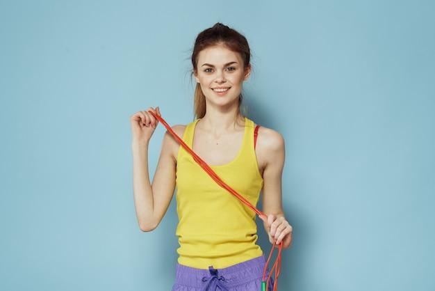 Sportive kobieta trzyma skakankę żółty podkoszulek gimnastyka niebieski podkoszulek