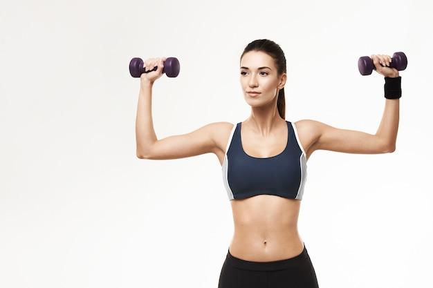Sportive kobieta w sportswear szkolenia rękach z dumbbells na bielu.