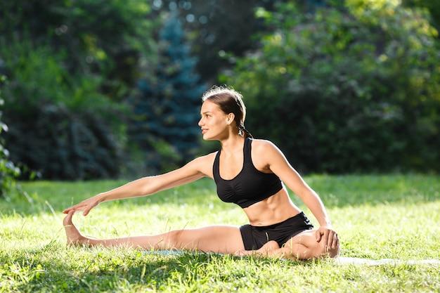 Sportive kobieta z brązowymi włosami na sobie czarny top i spodenki robi pozycję jogi w parku, zdrowy styl życia
