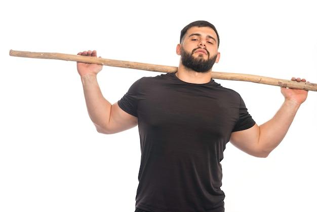 Sportive mężczyzna trzyma drewniany kij kung fu
