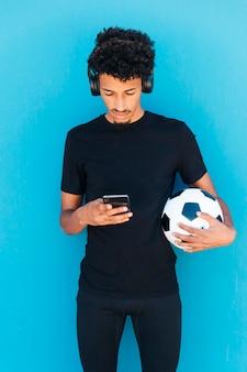 Sportive młody człowiek trzyma i używa telefon