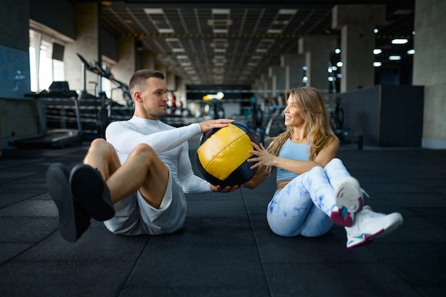 Sportive para robi ćwiczenia fitness z piłką, trening w siłowni. wysportowany mężczyzna i kobieta na treningu w klubie sportowym, aktywny zdrowy tryb życia, dobre samopoczucie fizyczne