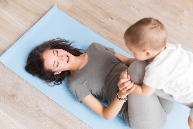 Sportive piękna matka w ciąży z synkiem ćwiczących na niebieskiej macie do jogi