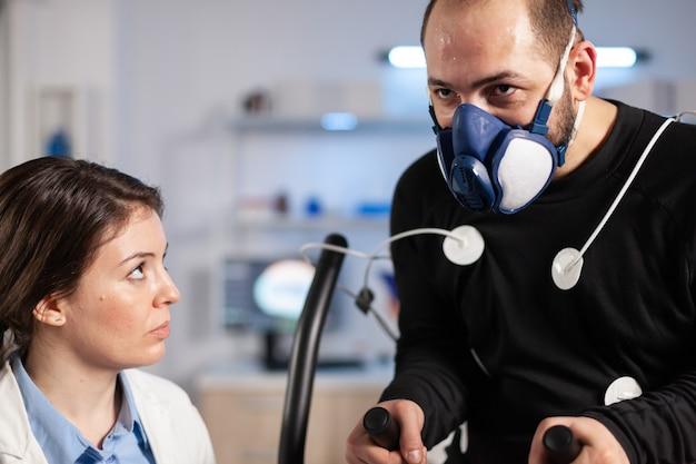 Sportman w laboratorium naukowym testujący wydajność cardio, naukowiec analizujący trening sportowca za pomocą czujników ciała. sportowiec na maszynie cross-maszyna badający sprawność.