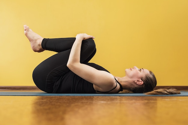 Sportowa atrakcyjna kobieta praktykuje jogę wykonując ćwiczenia apanasana na macie pod ścianą