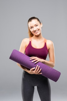 Sportowa atrakcyjna kobieta trzyma matę do jogi przed lub po zajęciach fitness na białym tle