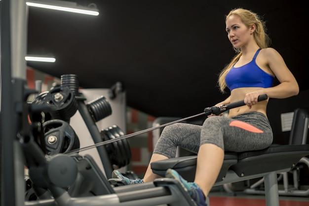 Sportowa bez koszuli kobieta robi treningi na plecach z maszyną do ćwiczeń siłowych w klubie siłowni.