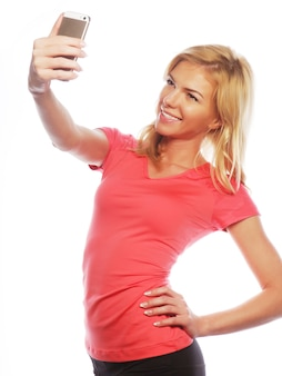 Sportowa blond kobieta robi selfie, strzał studio