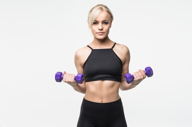 Sportowa blondynka młoda dziewczyna z fit muskularne ciało pracuje z hantlami w studio na białym tle