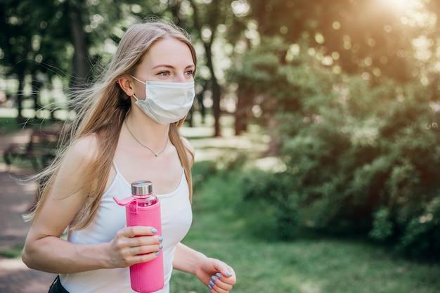 Sportowa blondynka w masce medycznej biegnie przez letni park