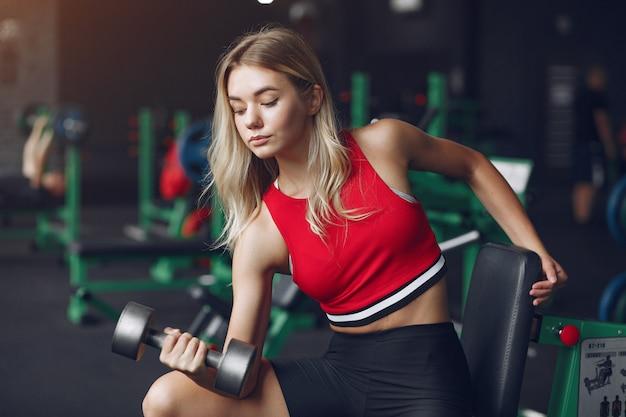 Sportowa blondynka w sportowym treningu na siłowni