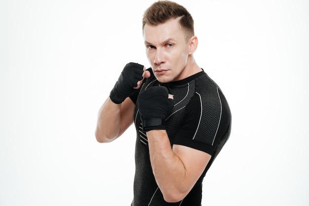 Sportowa boksera pozycja odizolowywająca nad biel ścianą