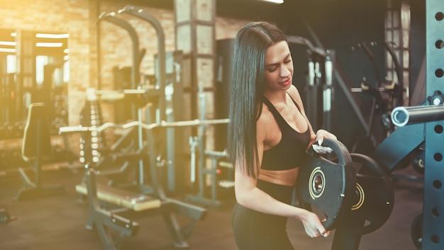 Sportowa brunetka kobieta kładąc dysk wagi na sztangę na tle siłowni