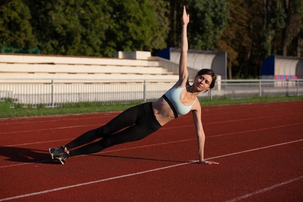 Sportowa brunetka kobieta w stroju sportowym robi ćwiczenia z deski bocznej na stadionie