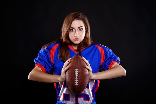 Sportowa brunetka pozuje jako futbol amerykański dziewczyna na czarnym tle
