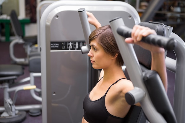 Sportowa brunetka używa ciężary maszynowe dla ręk